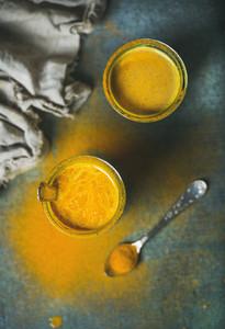 Golden milk with turmeric powder in glasses over dark background