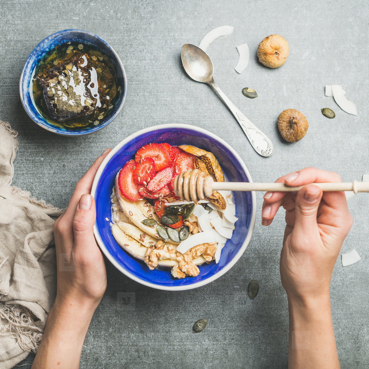 Blue bowl with healthy vegetarian breakfast in woman s hands
