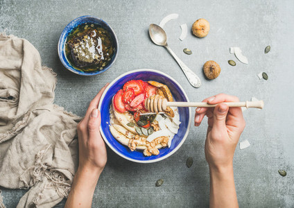 Blue bowl with healthy vegetarian breakfast ingredients in woman039 s hands