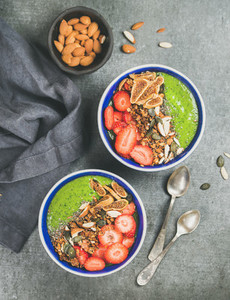 Healthy green smoothie breakfast bowls with granola  fruit  seeds  almonds
