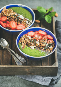 Green smoothie breakfast bowls with seeds nuts fruit and berries