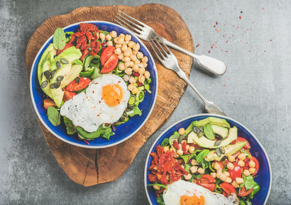 Healthy breakfast bowls with fried egg chickpea sprouts seeds vegetables
