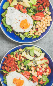 Close up of breakfast with fried egg  chickpea  vegetables  seeds  greens