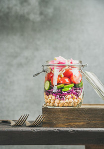 Healthy layered take away salad with vegetables and chickpea sprouts