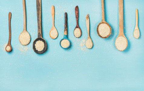 Quinoa seeds in different spoons over blue background  copy space