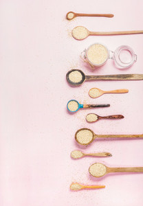 Quinoa seeds in different spoons and jar over pink background