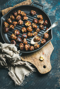 Roasted chestnuts in cast iron pan over dark blue background