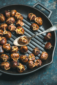 Close up of roasted chestnuts and spoon in grilling pan
