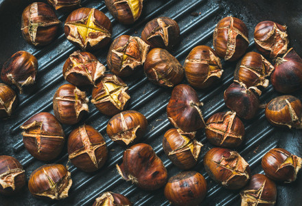 Roasted chestnuts over black cast iron grilling pan surface