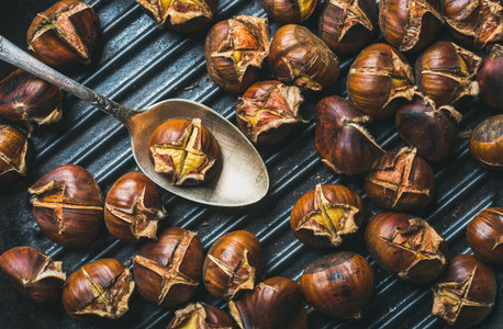 Close up of roasted chestnuts and metal vintage spoon in pan