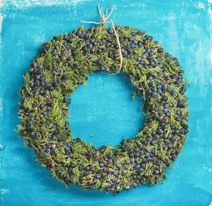 Christmas decorative wreath over bright blue painted wall background