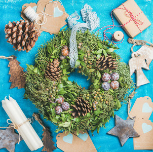 Christmas wreath  pine cones  toys  decorative materials over blue background