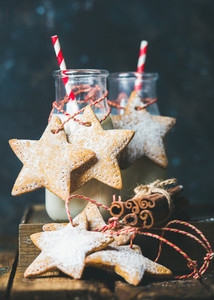 Bottles with milk and Christmas festive gingerbread star shaped cookies