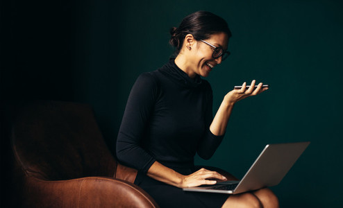 Businesswoman using laptop and mobile phone in office