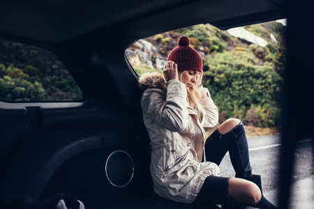 Beautiful woman sitting relaxed in car trunk