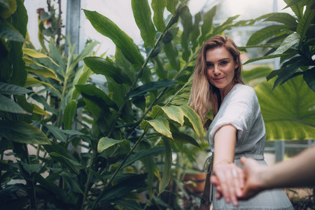 Beautiful woman with boyfriend in greenhouse