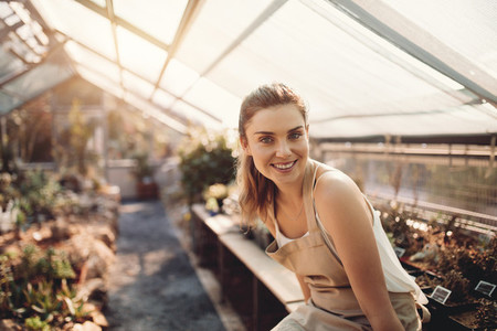 Beautiful woman working in greenhouse