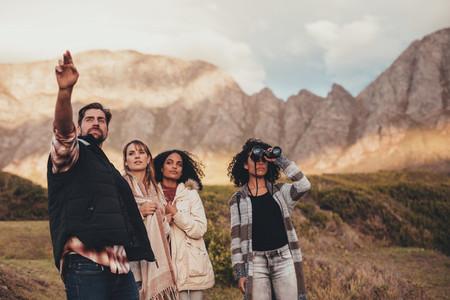 Friends on road trip admiring a landscape