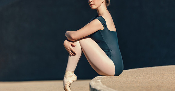 Close up of female ballet dancer sitting gracefully while restin
