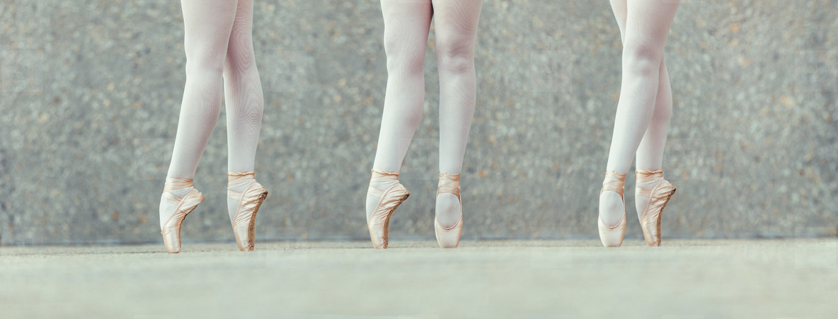 Closeup of legs of three ballet dancers in pointes