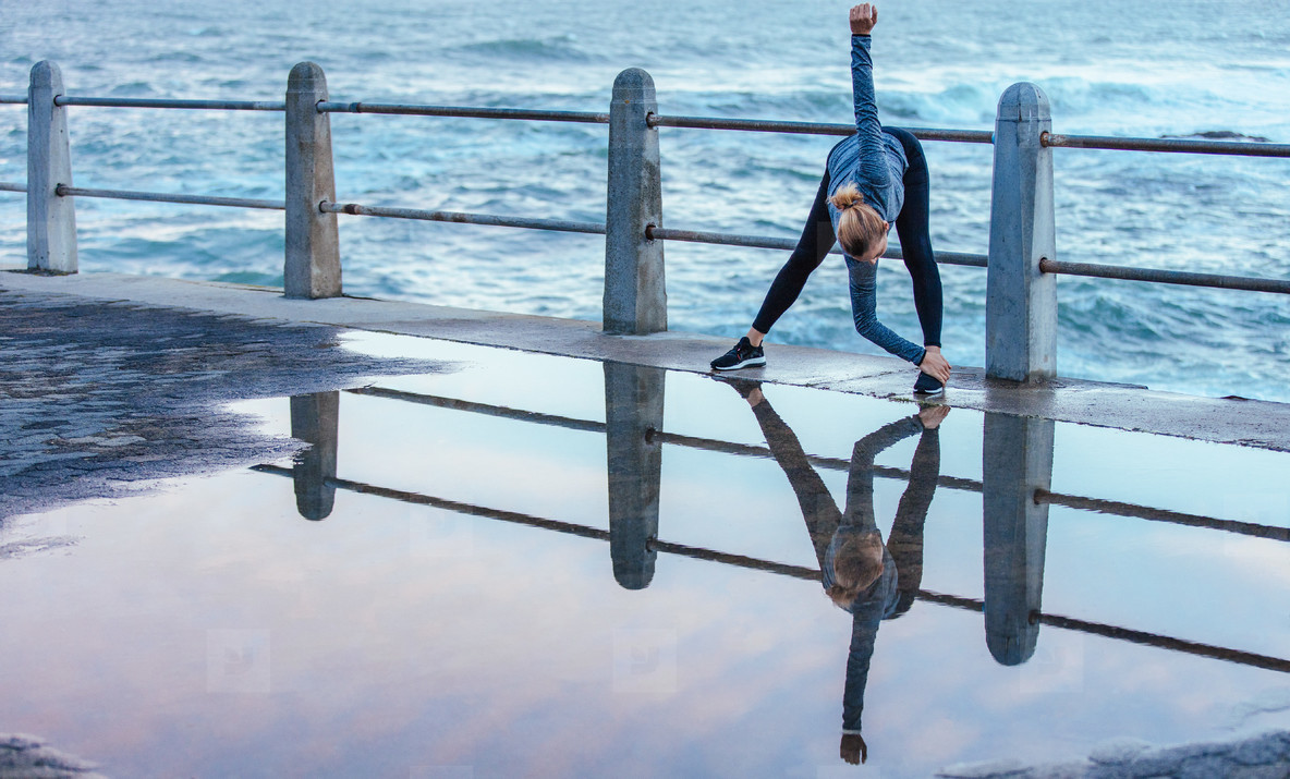 Reflection on wet road of woman doing stretches