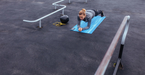 Fitness woman doing push ups at outdoor gym