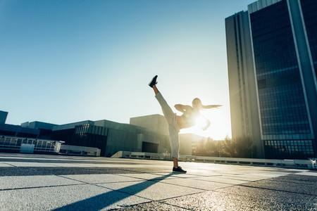 Urban woman doing high roundhouse kick