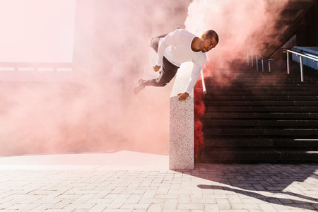 Man practicing parkour in urban space with smoke grenade