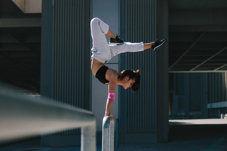 Woman doing handstand in city
