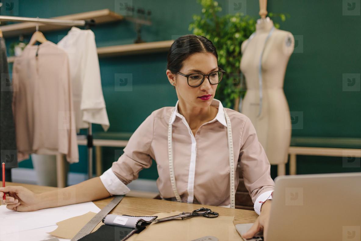 Creative fashion designer using laptop in her studio