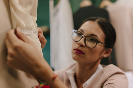 Fashion designer taking measurements on mannequin