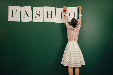 Woman arranging fashion word alphabets on wall