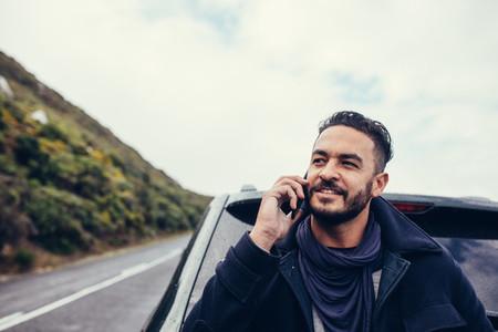 Man on road trip making a phone call
