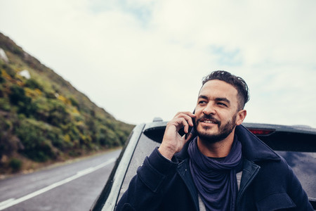 Man on road trip making a phone call