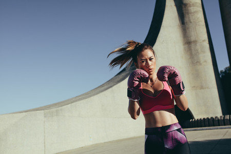 Young muscular woman practicing boxing