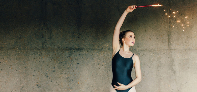 Female ballet dancer practicing dance moves using a firework