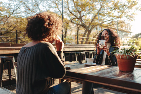 Two women friends drinking coffee and clicking photos