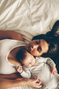 Mother and son sleeping together on bed
