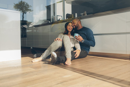 Romantic young couple sitting on kitchen floor in morning