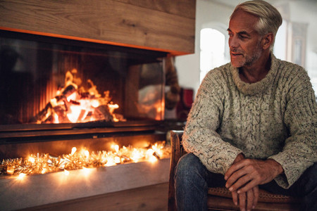 Mature man sitting by fire place in living room