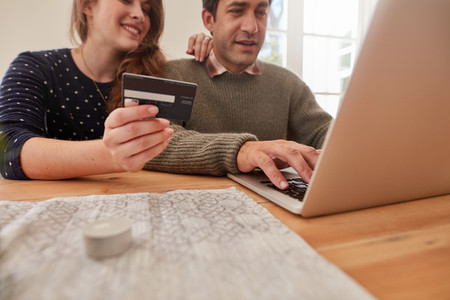 Young couple at home shopping online with credit card