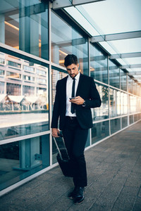 Handsome businessman using mobile phone at airport