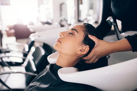 Hairdresser washing hair of customer at salon