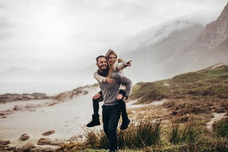 Couple piggybacking along the beach
