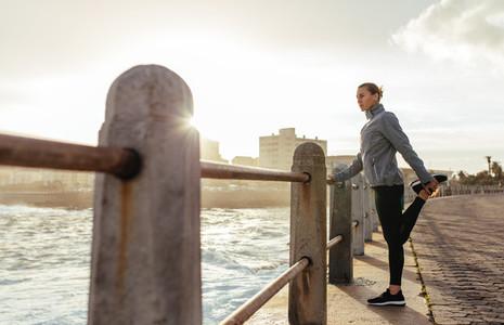 Woman runner doing stretching at seaside promenade