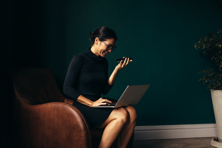 Young woman answering call and working on laptop