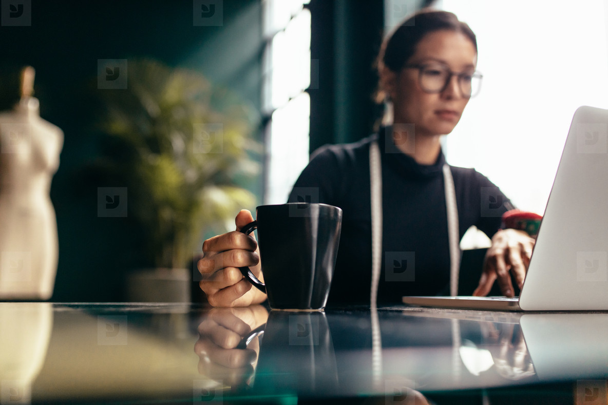 Female dressmaker working on laptop with cup of coffee