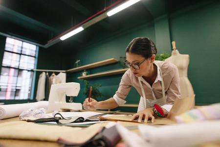 Female fashion designer drawing design sketch