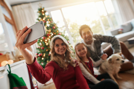 Young family talking selfie during Christmas at home