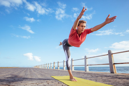 Woman doing virabhadrasana yoga pose at the seaside